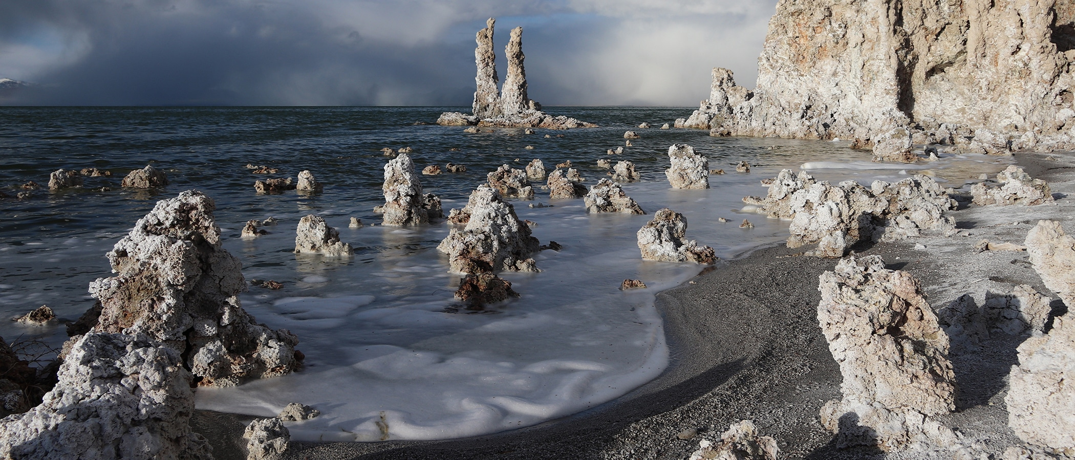 A storm brews in the distance behind a large grove of tufa towers on the shore of Mono Lake with a sandy peninsula dotted with smaller tufa mounds, in dramatic light, in the foreground.