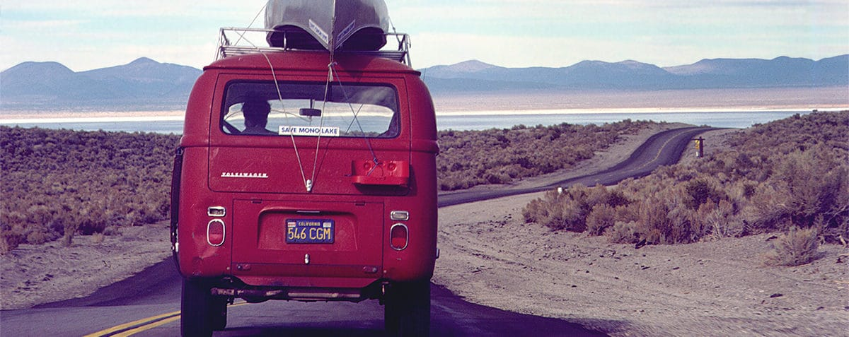 """A bright red Volkswagen van with a metal canoe strapped on top and a """"Save Mono Lake"""" bumper sticker drives down a two-lane highway towards Mono Lake in the distance."""