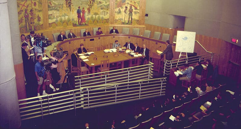 A hearing room with people seated in a semicircular room with reporters with large video cameras and a witness at the witness stand in front of a map display with Mono Lake on it.