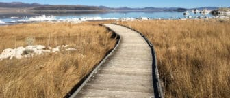 The end of a wooden boardwalk is surrounded by brown grasses and tufa, with glassy blue lake water behind it.