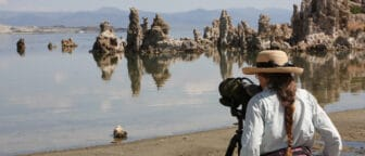 A woman on the shore of Mono Lake looking through a spotting scope out over the water with tufa towers in the background.